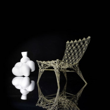 Knotted Chair miniature & egg vase Macramé meets high-tech. By a surprising marriage of handcraft and industrial technology this lightweight chair is born. The rope made of an aramide braid and carbon centre is knotted into the shape of a chair. The slack texture is then impregnated with epoxy and hung in a frame to harden. Gaudi revisited: gravity creates the final shape. The transparent appearance of the chair misleads you, the knotted fibre, which doesn't want to collapse looks strange, alien perhaps. The chair invites to touch and try. Despite all his modern technology he has a lovely doltishness, which bring out it's individual and personal character. Some products are a forerunner, a come out to new inventions, materials and technology. The knotted chair is such a product. Jury-report Rotterdam design prize 1997, 'Knotted Chair' by Marcel Wanders appeals to the imagination because it realizes the designer's age-old dream: making something soft and flat become rigid and three-dimensional by means of a couple of technical inventions. Moreover he rescues the traditionally pure, practical and constructive macramé technique from stuffy image that it has had since the Sixties by linking it up with the latest technology. The knotted chair is selected and presented for the Cappellini Collection. The Museum of Modern Art New York amongst many others buys the chair. The Chair won the prize of the public of the Rotterdam design prize and Wanders won the Kho Liang I incentive prize for industrial design with it. Material: aramide carbon rope, epoxy Dimensions: 72 x 56 cm x D: 65 cm (h x w x d) Design: 1996 Distributed by Cappellini, Italy